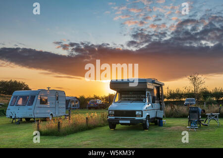 The sun sets behind a Motorhome on a popular campsite after a beautiful summers day in North Devon. - Stock Photo
