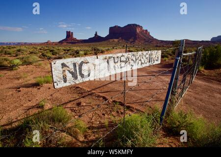 No trespassing sign on fence in Monument Valley at sunset - Stock Photo