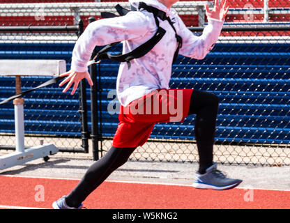 High school track and field runner is sprinting while strapped up to and pulling a weighted sled behind him. - Stock Photo