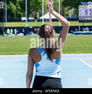 A high school girl holding a javelin overhead as she gets ready to compete in a track and field event. - Stock Photo