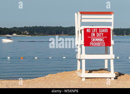 An empty lifeguard stand with a sign that saying no life guard on duty swimming is prohibited on the north shore of Long Island and a boat moving in t - Stock Photo