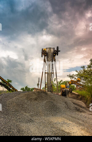 Industrial extraction of stone machine working in the stone mine with Moody sky. - Stock Photo