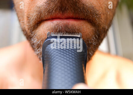 Hair clipper used to trim a man's beard with little money to save himself from going to the hairdresser. - Stock Photo