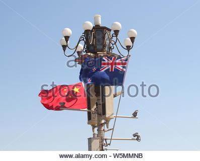 National flags of China and New Zealand flutter on a