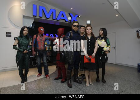 Chinese filmgoers wearing costumes of Avengers superheroes wait inside a cinema before the midnight premiere of Disney and Marvel's 'Avengers: Endgame - Stock Photo