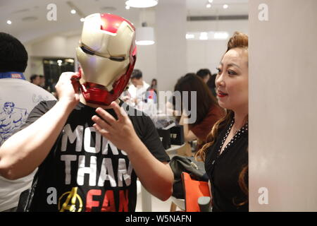 A Chinese filmgoer wearing the Iron Man helmet waits inside a cinema before the midnight premiere of Disney and Marvel's 'Avengers: Endgame' in Shangh - Stock Photo