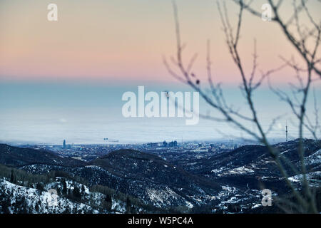 Foggy Almaty city view from the mountains at winter in Kazakhstan, Central Asia - Stock Photo