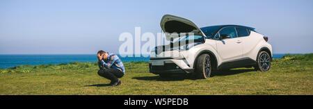 Young man desperate, car broken down - Stock Photo