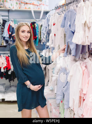 A pregnant woman chooses children's clothes in the store - Stock Photo