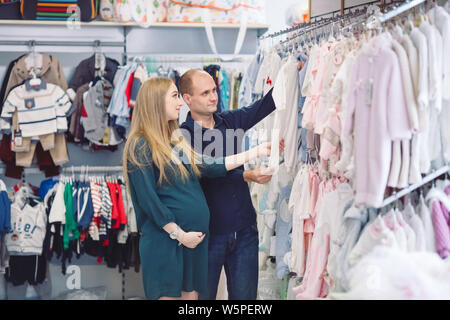 Pregnant woman with husband shopping for baby. - Stock Photo