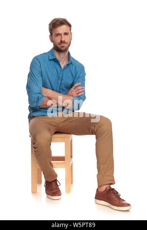 serious young casual man sitting with hands crossed on white background - Stock Photo