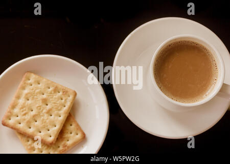 Tea cup and plate with stack of cream cracker biscuits isolated black background. Top View. Close up picture. Chinese tea cup, tasty biscuit cookies. - Stock Photo