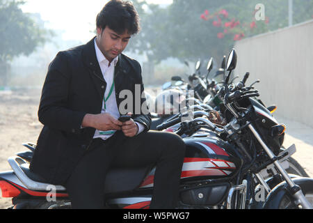 Salesman sitting on a motorcycle and using mobile phone - Stock Photo