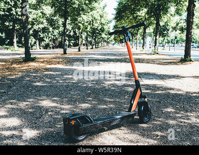 rental e-scooter, motorized scooter, parked in public park in Berlin, Germany - Stock Photo