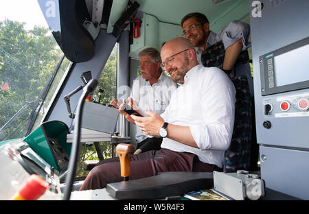 29 July 2019, Brandenburg, Potsdam: Potsdam's Lord Mayor Mike Schubert (r, SPD), Thomas Kralinski (r, SPD), State Secretary and Digital Coordinator of the State of Brandenburg, are waiting at the depot of Verkehrsbetrieb Stadtwerke Potsdam (ViP) for the start of a test drive of the first autonomous tram 'Combino 400 Perugia' next to the driver Norbert Gräsing (l). For safety reasons, a driver is always seated in the cab during test drives who can intervene in the driving process. Passengers were not allowed to board at the stops. The mayor of the city and the digital coordinator of the country - Stock Photo