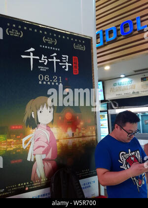 --FILE--A filmgoer waits in front of a poster of Japanese animated film 'Spirited Away' at a cinema in Yichang city, central China's Hubei province, 1 - Stock Photo