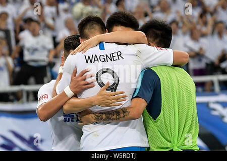 German football player Sandro Wagner, center, of Tianjin TEDA celebrates with his teammates after scoring against Shandong Luneng Taishan in their 14t - Stock Photo