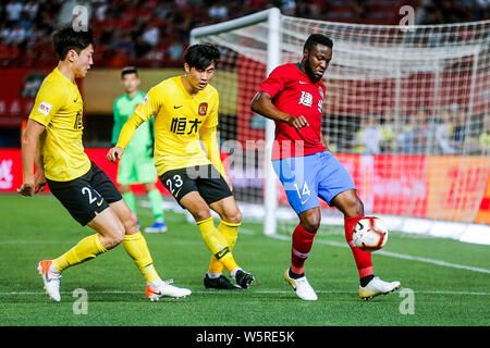 Cameroonian football player Franck Ohandza, right, of Henan Jianye passes the ball against players of Guangzhou Evergrande Taobao in their 12th round - Stock Photo