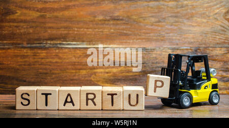 Forklift truck carries a letter block P to inscription Startup. The concept of raising funds for a startup. Crowdfunding. Raising funds and resources - Stock Photo