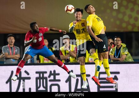 English football player Tyias Browning, top, of Guangzhou Evergrande Taobao heads the ball against Cameroonian football player Franck Ohandza of Henan - Stock Photo