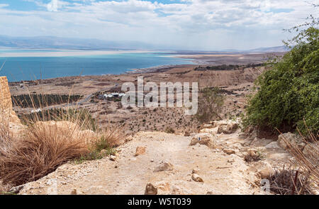 a hiking trail between the vegetation and the ancient mamluk flour mill at the ein gedi spring with the kibbutz and the dead sea in the background - Stock Photo