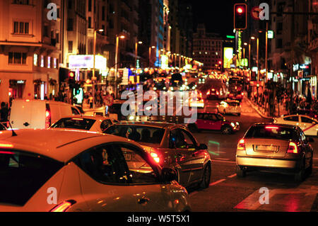 Car traffic in west part of famous Gran Via, main street in Madrid. Evening shot with city lights - Stock Photo
