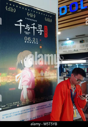 --FILE--A filmgoer waits in front of a poster of Japanese animated film 'Spirited Away' at a cinema in Yichang city, central China's Hubei province, 2 - Stock Photo