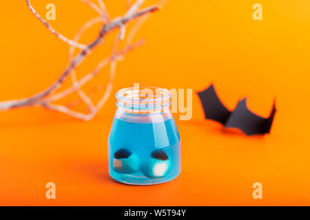 Halloween concept - two artificial eyes in a blue liquid on a orange background with bat and branches on a background - Stock Photo