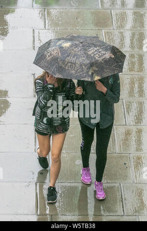 London, UK. 30th July 2019. Pedestrians shelter  from the rain in Waterloo as a month's rainfall is expected to fall in three hours  Credit: amer ghazzal/Alamy Live News - Stock Photo