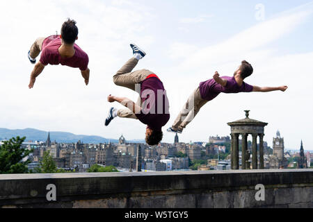 Edinburgh, Scotland, UK. 30 July 2019. Artists from the Barely Methodical Troupe perform on Calton Hill in Edinburgh ahead of their debut show  Bromance that is being performed during the during the Edinburgh Festival this year. L to R Louis Gift, Beren D'Amico, Charlie Wheeler Credit: Iain Masterton/Alamy Live News - Stock Photo