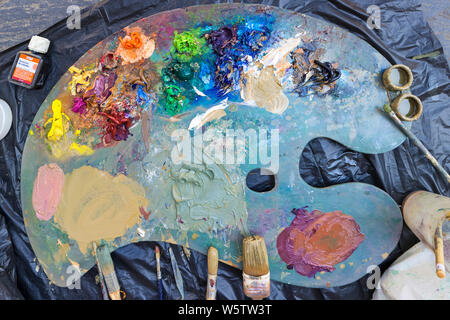A Painter's Palette with Paints and Brushes. - Stock Photo
