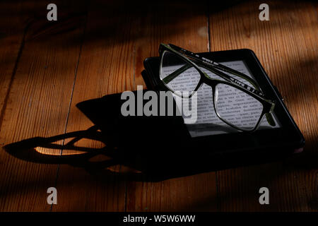 Electronic book and reading glasses. An anti-reflex electronic ink device that provides a comfortable reading experience on the device. - Stock Photo