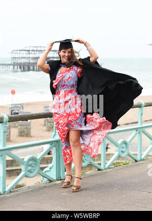 Brighton, UK. 30th July, 2019. Lois Green hangs on to her mortar board after graduating from the University of Brighton on a windy seafront after the ceremony . Credit: Simon Dack/Alamy Live News - Stock Photo