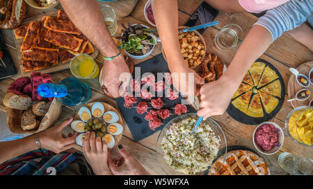 Evening with friend dinner on the terrace enjoying together. Summer aperitif with group of friends Joy and festivities in family View from the top of - Stock Photo