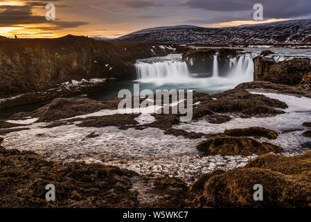 Melted glacier water flowing in frozen godafoss waterfalls at sunrise, Iceland - Stock Photo