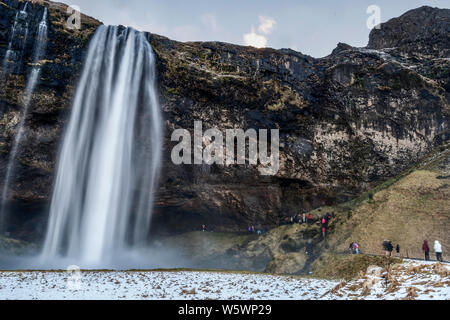 Tourists enjoying cold water breeze from Seljalandsfos waterfall during winter season in Iceland - Stock Photo