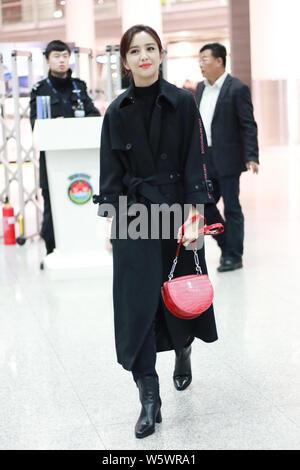Chinese actress Tong Liya arrives at an airport before departure in Shanghai, China, 29 November 2018.   Coat: Emporio Armani  Handbag: Bally - Stock Photo