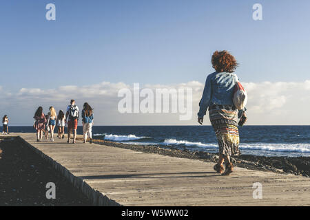 Group of people walking on a wooden path near the sea. Tourists back home after day at the beach.  Friends enjoying a beautiful summer evening togethe - Stock Photo