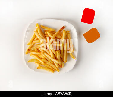 Serving French fries on a white background with two packs of sauce top view. Close-up. Potato Garnish - Stock Photo
