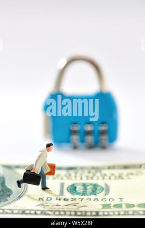 Miniature people: businessman walking on money with key lock blur background (this image for security on financial and business concept) - Stock Photo