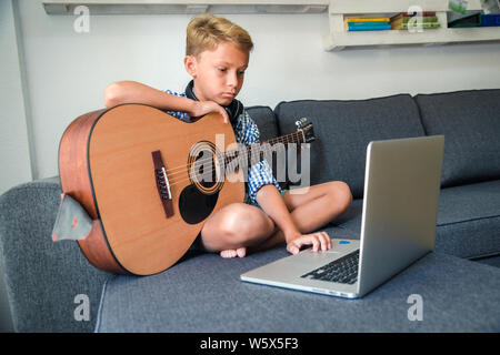 Beautiful young boy playing acoustic guitar searching songs on the laptop to exercise alone at home. Trendy caucasian child plays instruments sitting - Stock Photo