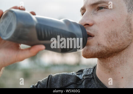 portrait of a young Caucasian guy in a black t-shirt and black shorts drinking water from a bottle after or before training - Stock Photo