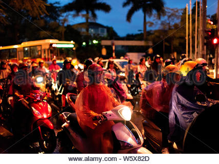 HANOI, VIETNAM; SEPTEMBER 26, 2018: Young woman with a mask waiting on her motorbike with more biker to turn green the traffic light on a rainy day - Stock Photo
