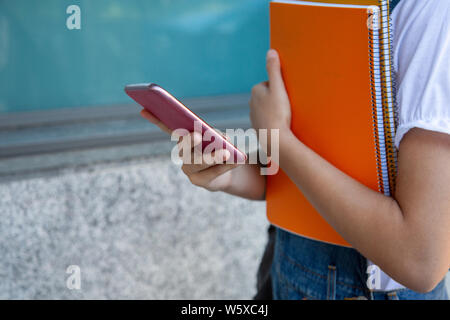 Student girl holding notebooks using her smartphone at the college. Unrecognizable person - Stock Photo