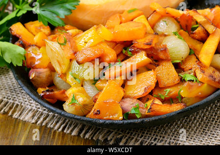 Fried pumpkin, onion, garlic and pepper in frying pan, close up view - Stock Photo