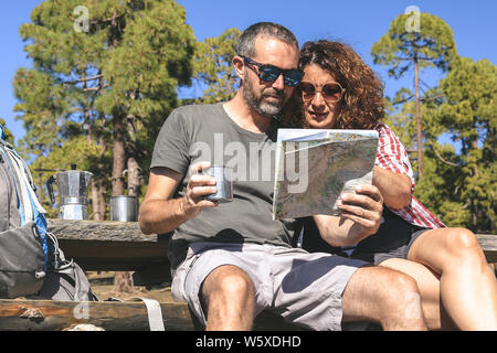 Couple taking a rest after mountain trekking Man and woman looking the map to find the hiking path Caucasian people drink coffee in a sunny day at the - Stock Photo