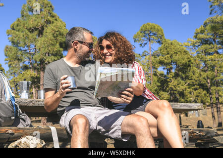 Smiling couple taking a rest after mountain trekking Man and woman looking the map to find the hiking path Happy caucasian people drink coffee at the - Stock Photo