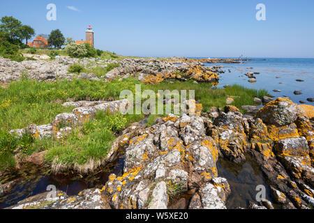 Svaneke Gamle Fyr lighthouse and rocky coastline along east coast, Svaneke, Bornholm Island, Baltic sea, Denmark, Europe - Stock Photo