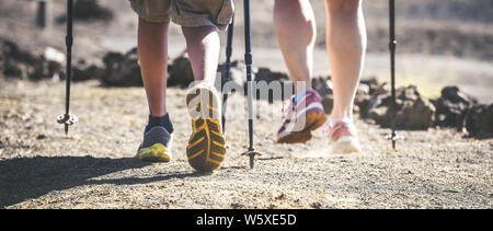 Close up panorama view of mother and son feet walk on a mountain path with trekking shoes and hiking poles Frog perspective of a couple with walking s - Stock Photo
