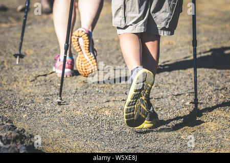 Close up back view of mother and son feet walk on a mountain path with trekking shoes and hiking poles Frog perspective of a couple with walking stick - Stock Photo